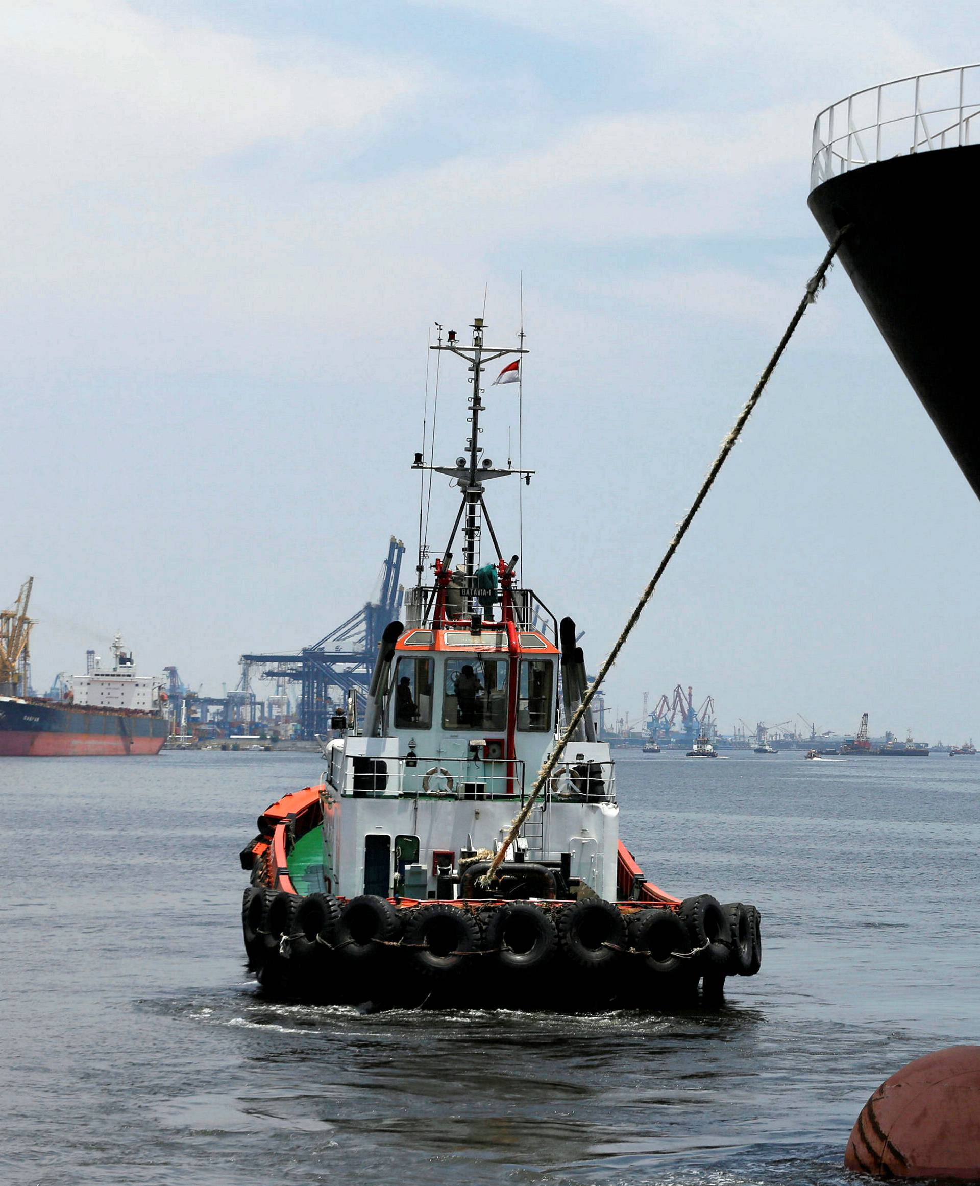 A cargo ship is towed in by a tugboat in Tanjung Priok Port, Jakarta, Indonesia