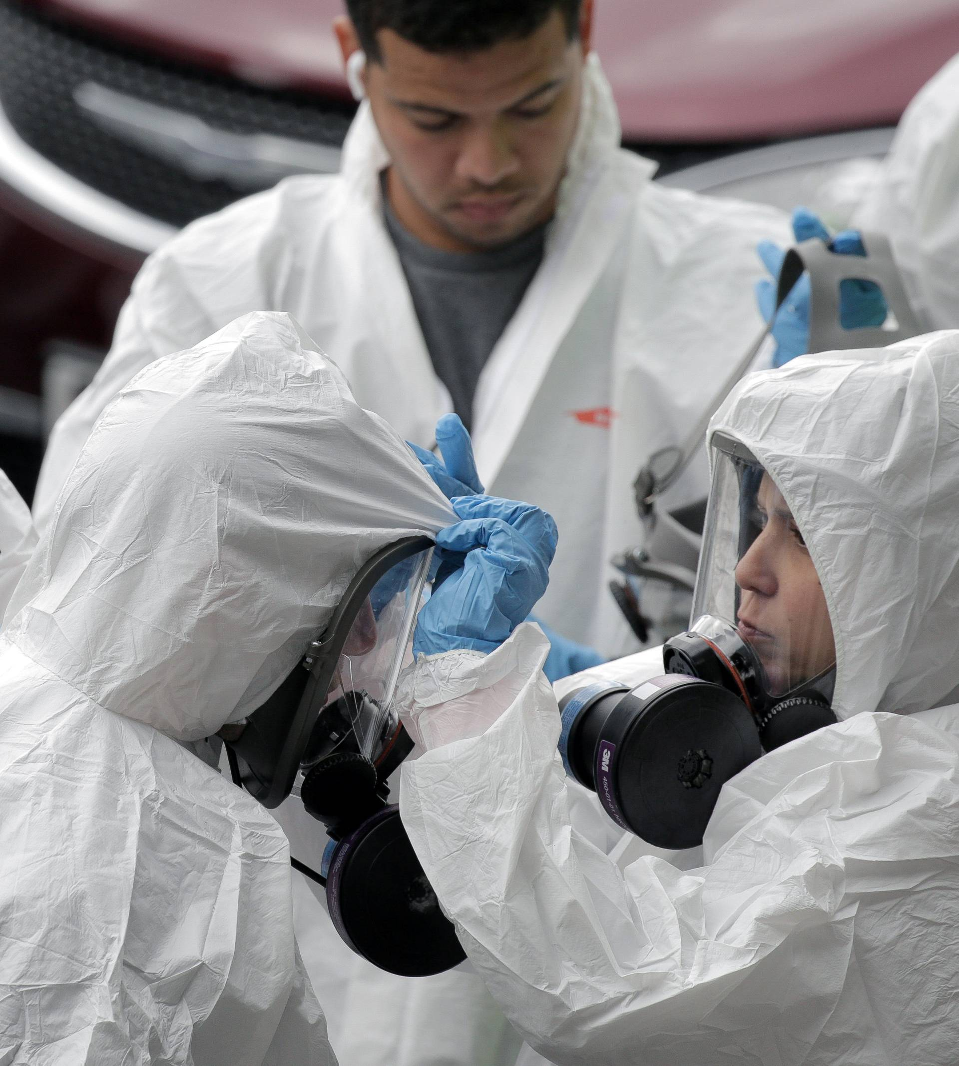 Members of a cleaning crew prepare to enter the Life Care Center of Kirkland, the Seattle-area nursing home at the epicenter of one of the biggest coronavirus outbreaks in the United States, in Kirkland