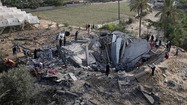 Palestinians gather around the remains of a house destroyed in an Israeli air strike in the southern Gaza Strip