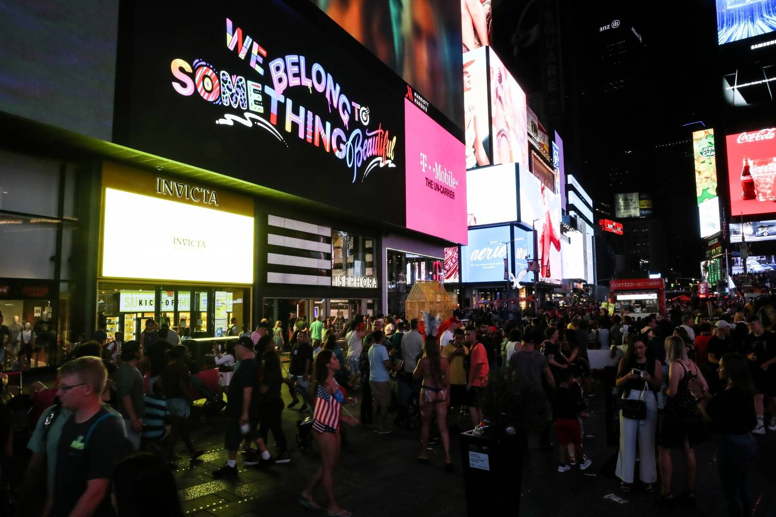 People walk near Times Square area after power was restored following a blackout that affected buildings and traffic during widespread power outages in the Manhattan borough of New York