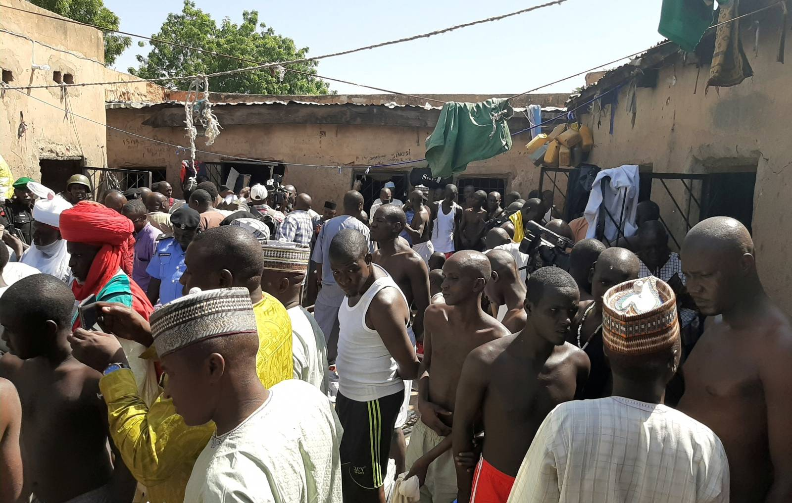 Police officers, journalists and a traditional chief stand next to people who were rescued by police in Sabon Garin, in Daura local government area of Katsina state