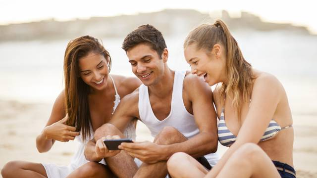 Friends using a smart phone on the beach