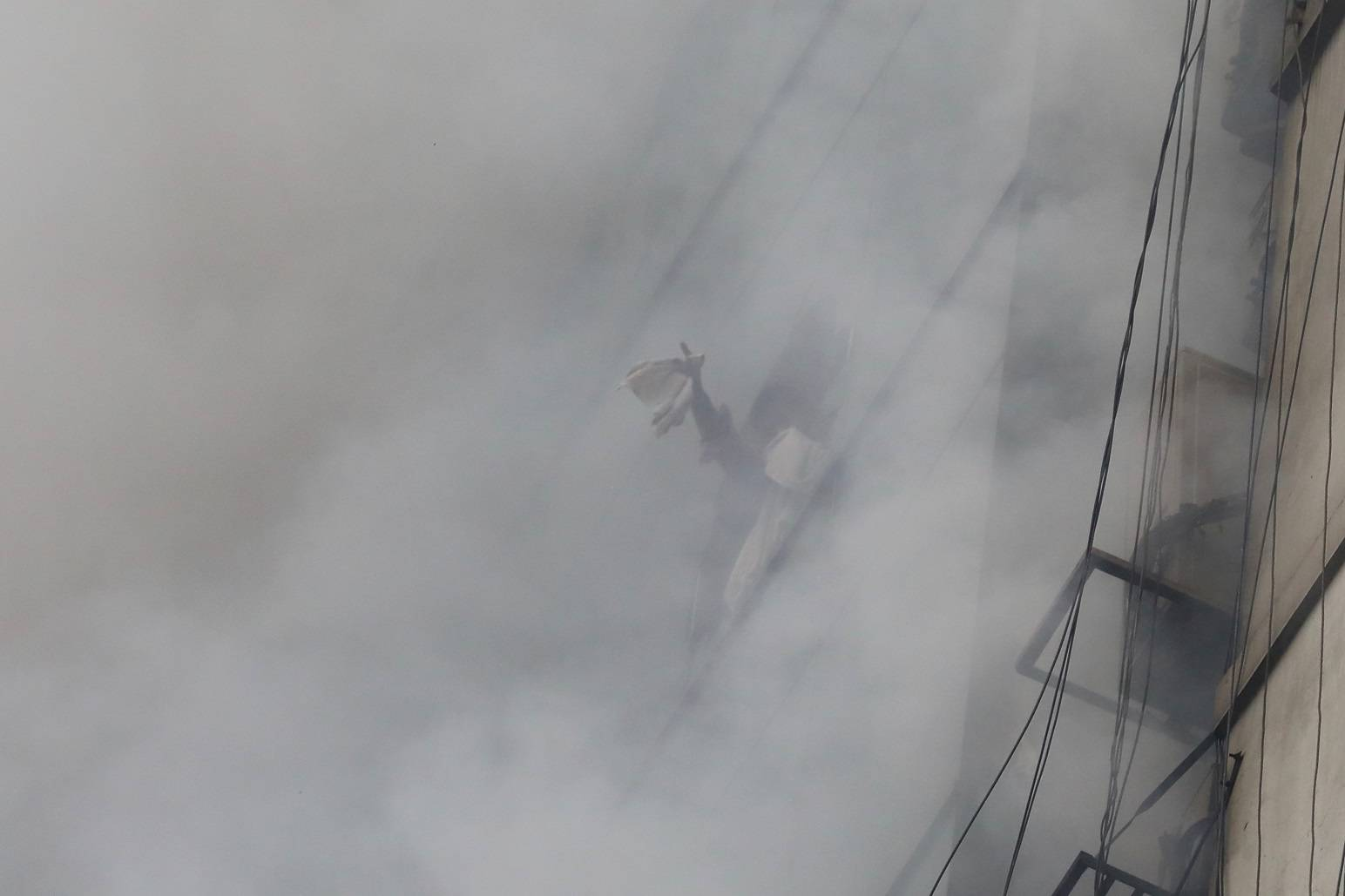 A trapped person waves to be rescued as fire broke out at a multi-storey commercial building in Dhaka