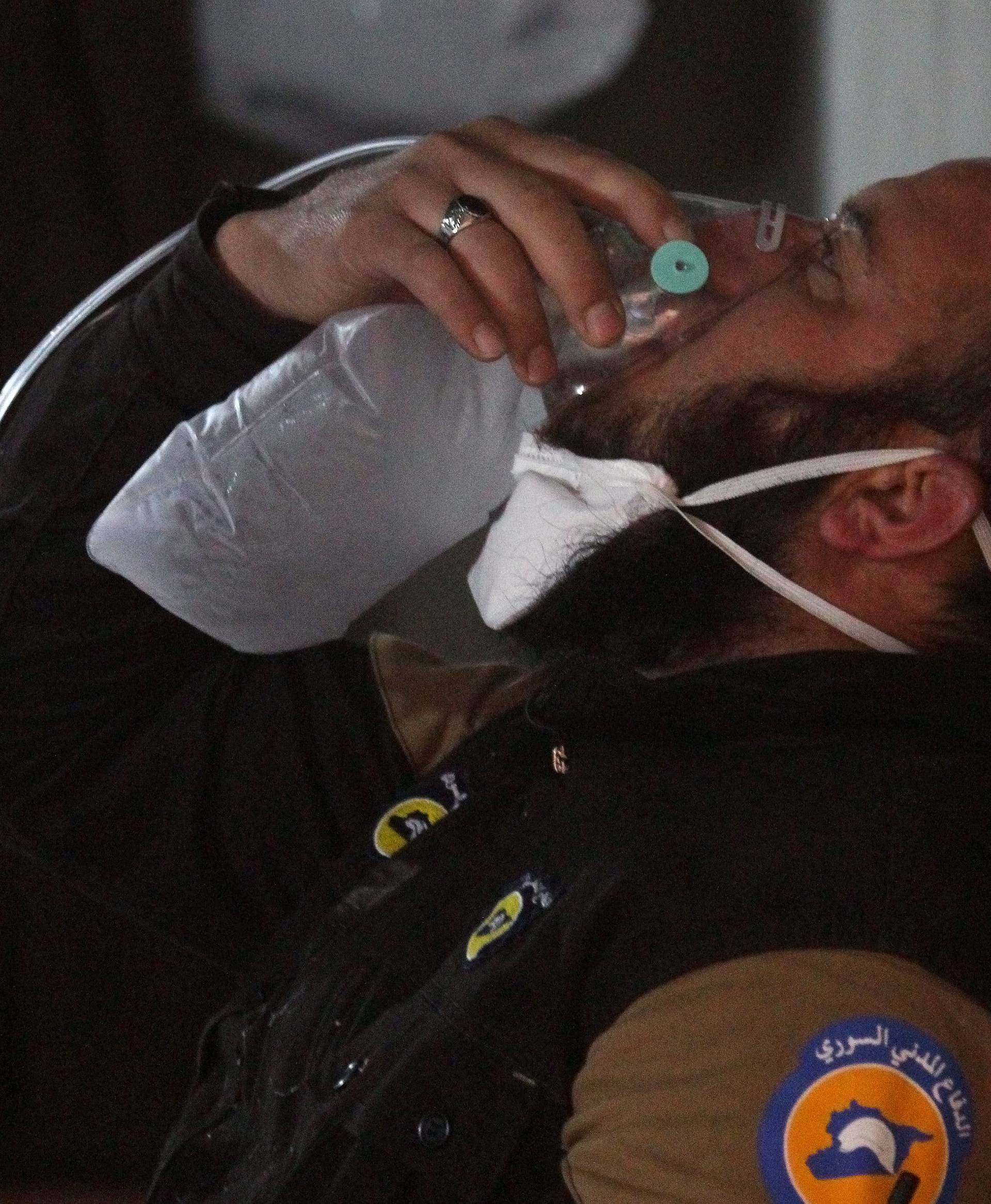 A civil defense member breathes through an oxygen mask, after what rescue workers described as a suspected gas attack in the town of Khan Sheikhoun in rebel-held Idlib