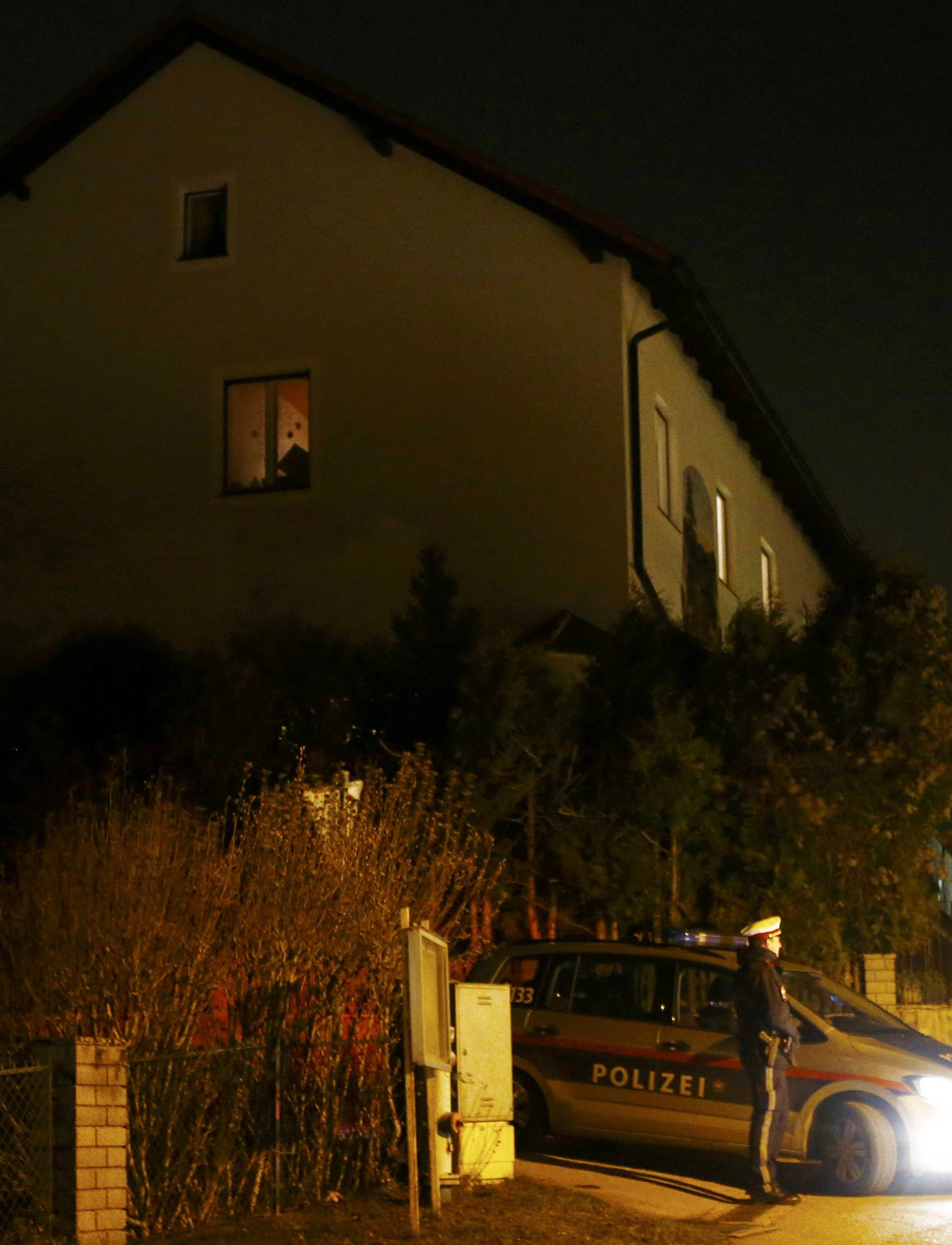 Police stand in front of a house where six people were found dead in Boeheimkirchen
