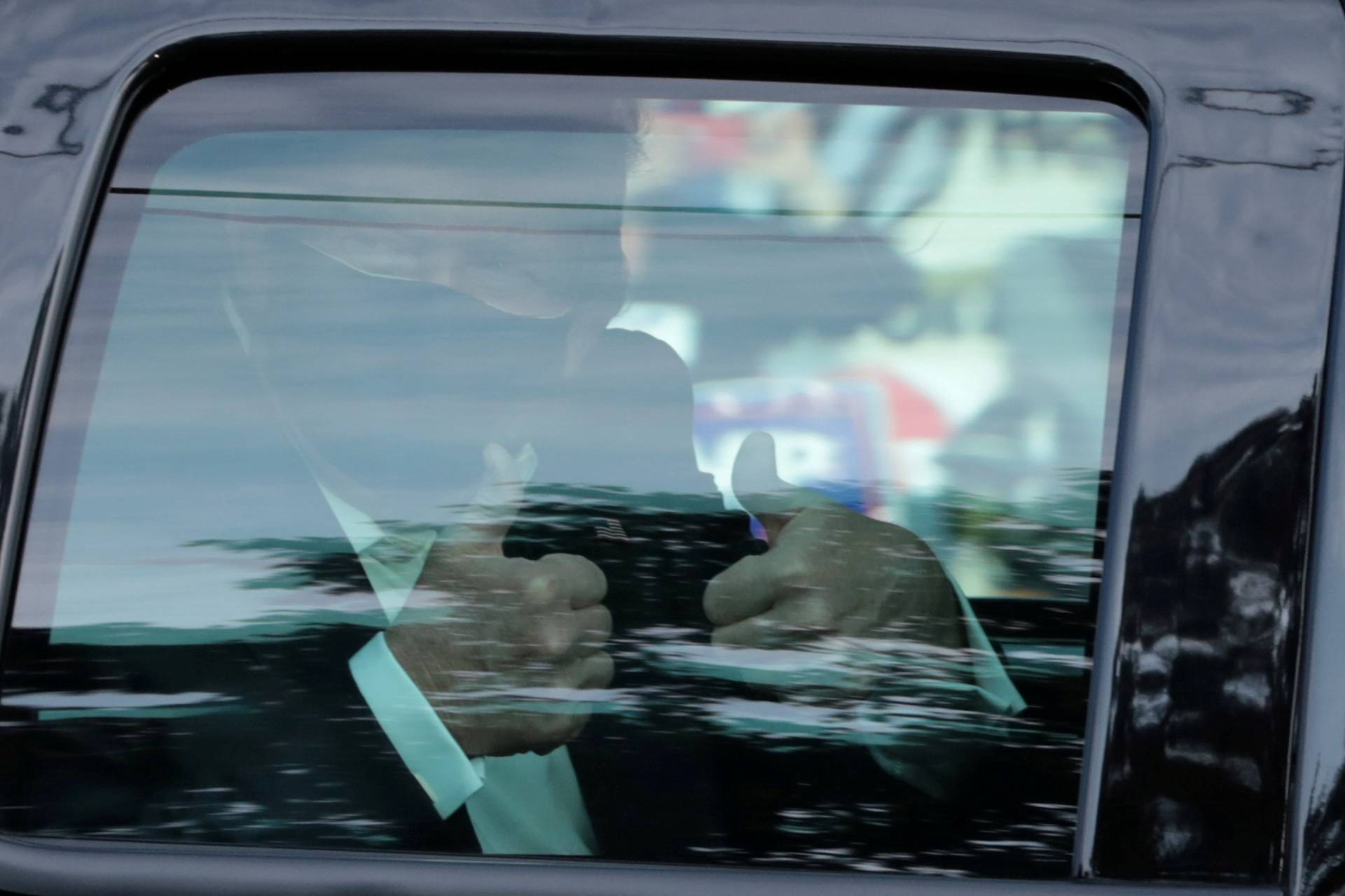 FILE PHOTO: U.S. President Donald Trump gestures from a car as he rides in front of  the Walter Reed National Military Medical Center, where he is being treated for the coronavirus disease (COVID-19) in Bethesda, Maryland