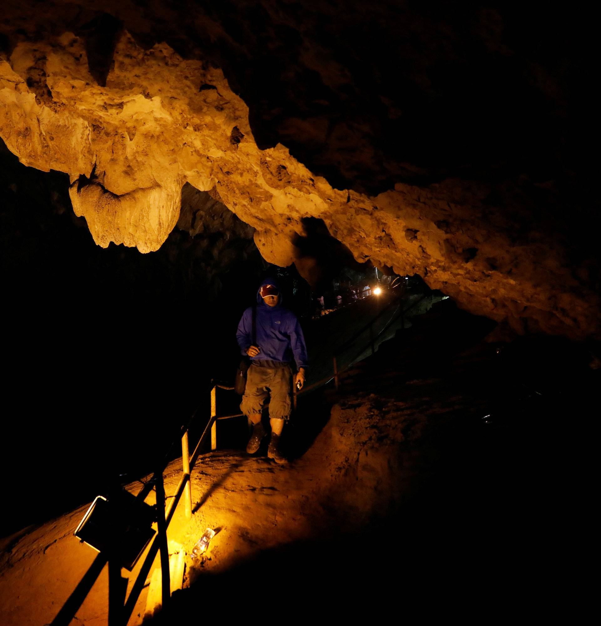 A rescue worker walks in Tham Luang caves during a search for 12 members of an under-16 soccer team and their coach, in the northern province of Chiang Rai