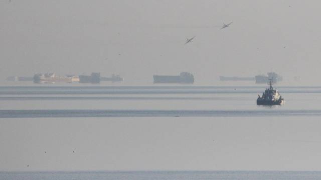 Russian jet fighters fly over vessels after the channel beneath a bridge connecting the Russian mainland with the Crimean Peninsula was blocked to stop three Ukrainian navy ships from entering the Sea of Azov via the Kerch Strait in the Black Sea