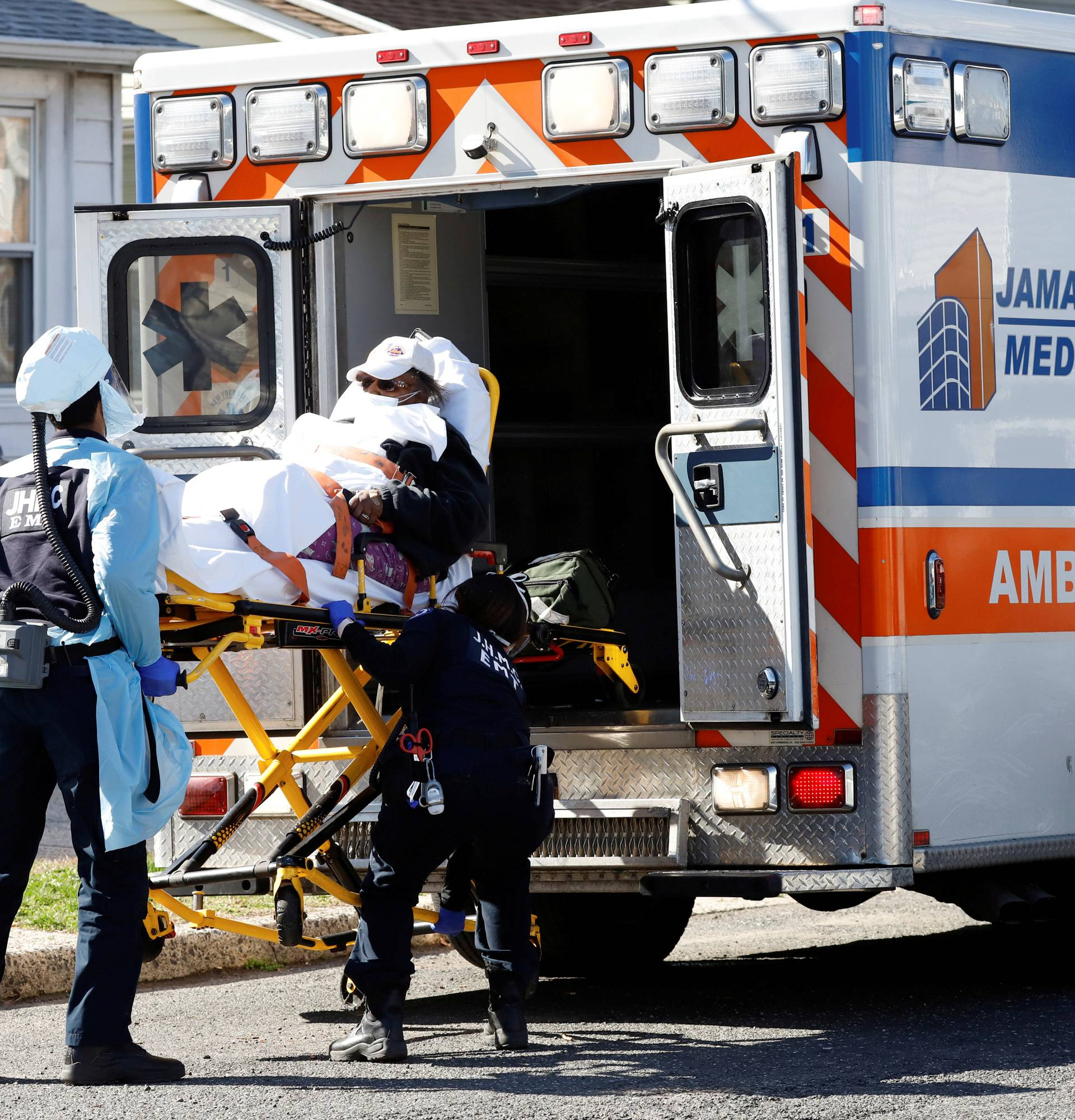 FILE PHOTO: Emergency Medical Technicians (EMT) lift a patient into an ambulance as the the outbreak of coronavirus disease (COVID-19) continues, in New York