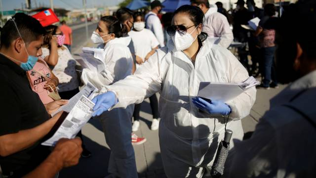 Personnel of an assembly factory, in protective gear, hands out job application forms to job seekers as the coronavirus disease (COVID-19) outbreak continues in Ciudad Juarez