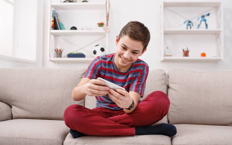 Teenager playing games on smartphone