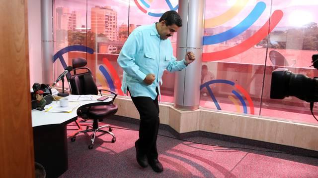 Venezuela's President Nicolas Maduro dances during his radio program at Miraflores Palace in Caracas