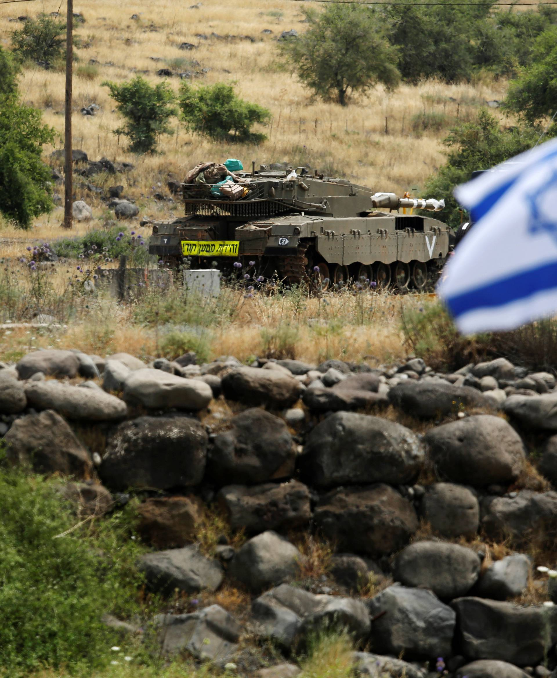 An Israeli tank can be seen near the Israeli side of the border with Syria in the Israeli-occupied Golan Heights
