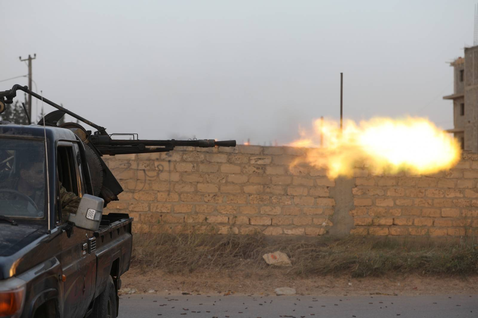 Members of the Libyan internationally recognised government forces fire during fighting with Eastern forces in Ain Zara