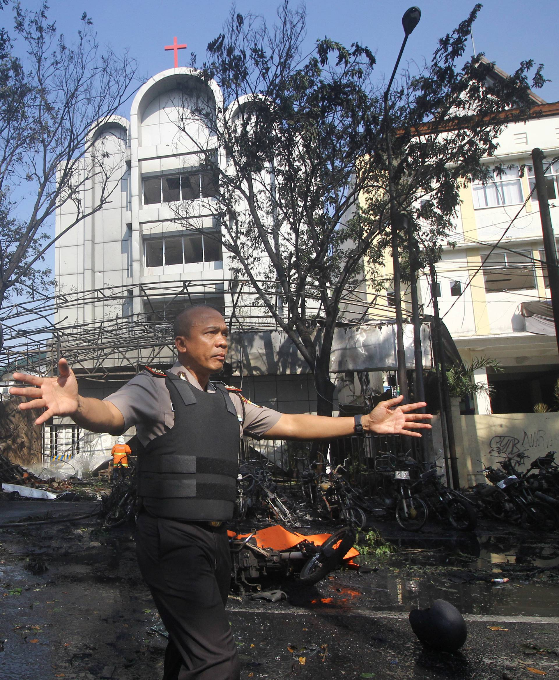 Police stand guard near the site of a blast at the Pentecost Church Central Surabaya (GPPS), in Surabaya, East Java,