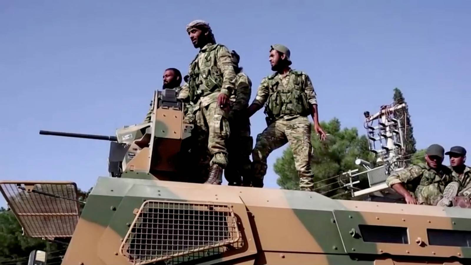 Syrian rebels stand on top of an armoured vehicle driving towards the border to cross into Syria, in Ceylanpinar