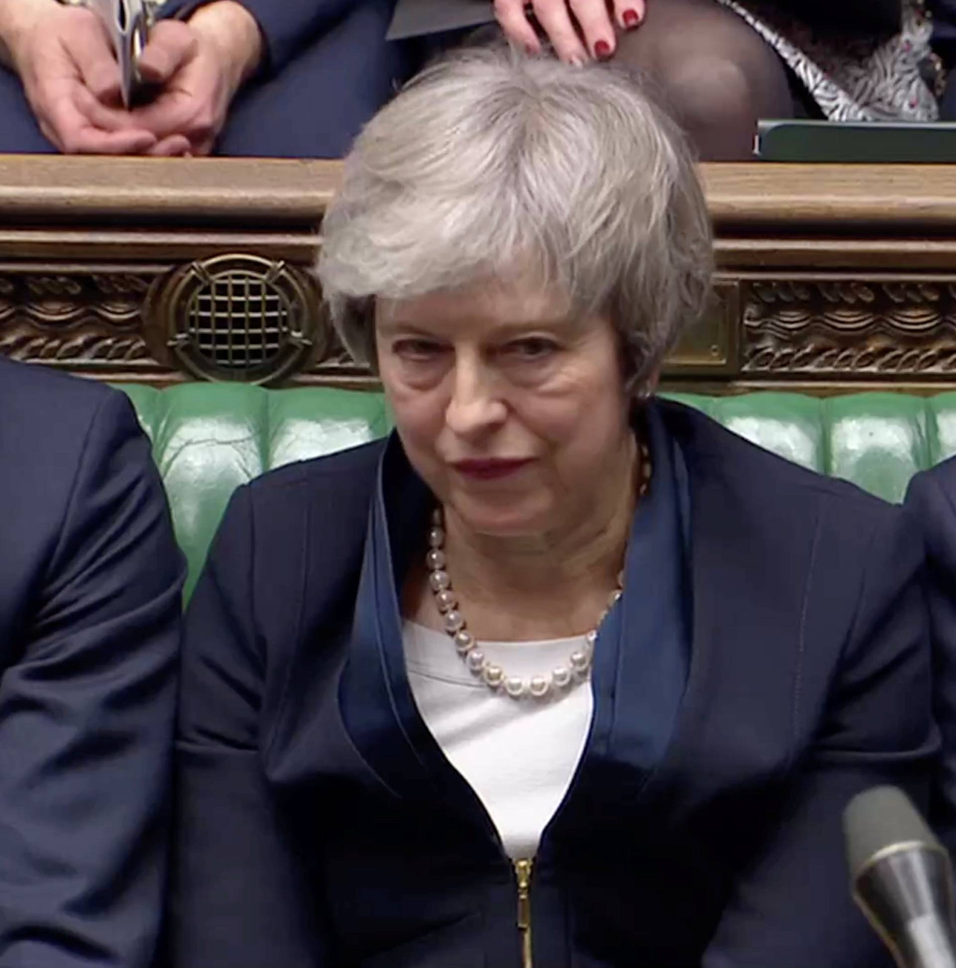 Prime Minister Theresa May sits down in Parliament after the vote on May's Brexit deal, in London