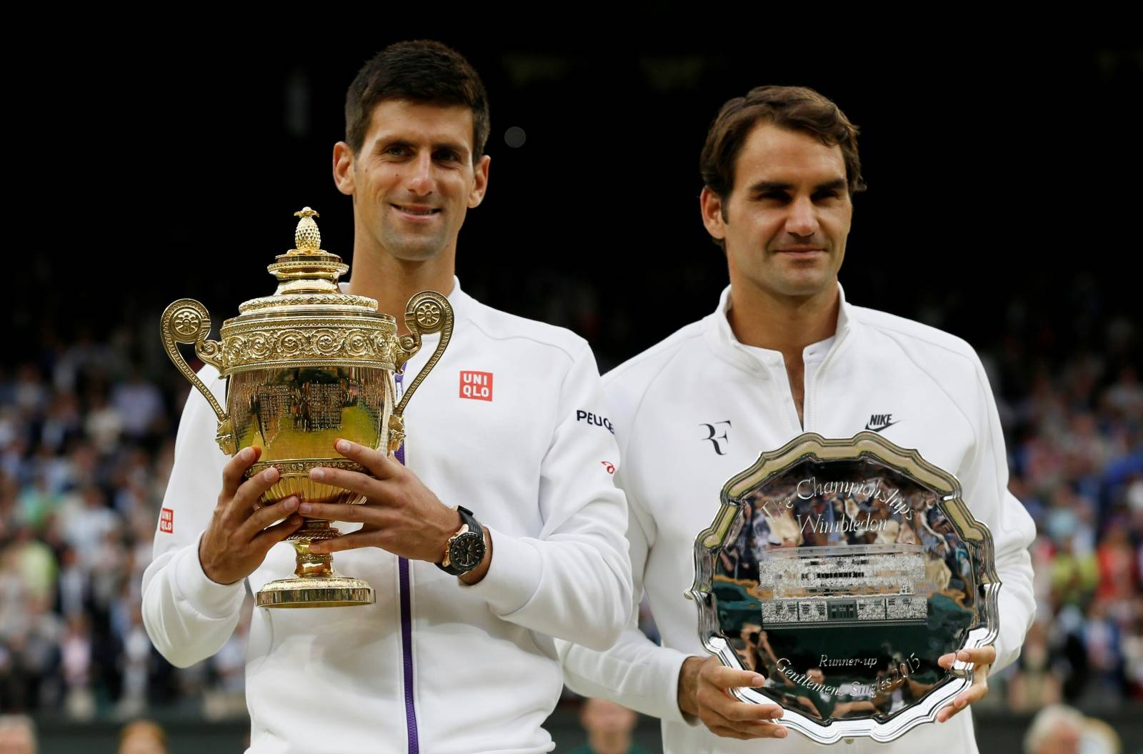 FILE PHOTO: Winner, Novak Djokovic of Serbia and runner up Roger Federer of Switzerland pose with their trophies after their Men's Singles Final match at the Wimbledon Tennis Championships in London