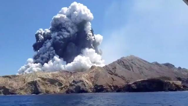 Smoke from the volcanic eruption of Whakaari, also known as White Island, is pictured from a boat
