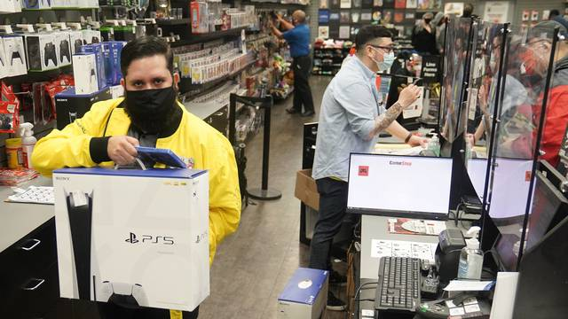 Inside a GameStop store a worker takes a Sony PS5 gaming console to the counter to sell