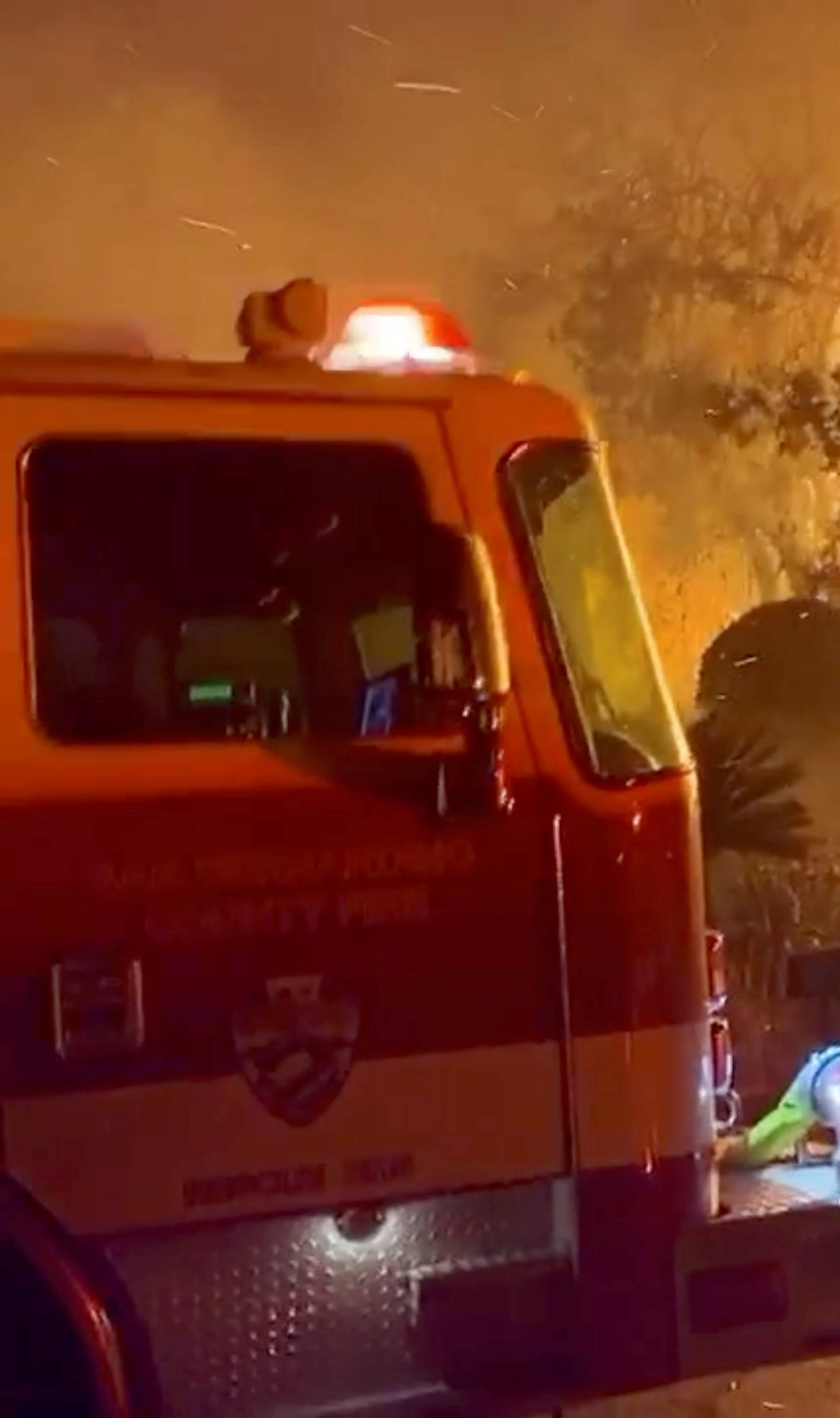 A firefighter passes by a fire engine in front of a burning house during wildfires in San Bernardino, California