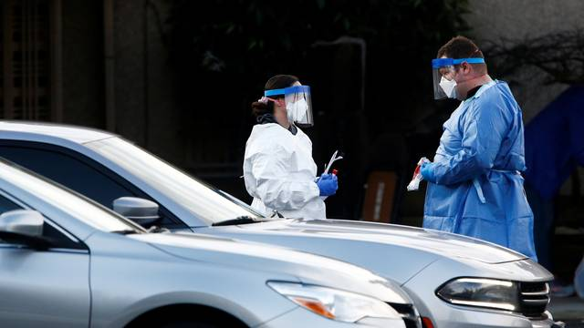 Nurses in protective gear talk before administering a drive-through nasal swab test at Life Care Center of Kirkland