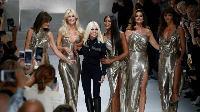 Italian designer Donatella Versace acknowledges the applause with former top models Carla Bruni, Claudia Schiffer, Naomi Campbell, Cindy Crawford and Helena Christensen at the end of Versace Spring/Summer 2018 show at the Milan Fashion Week in Milan