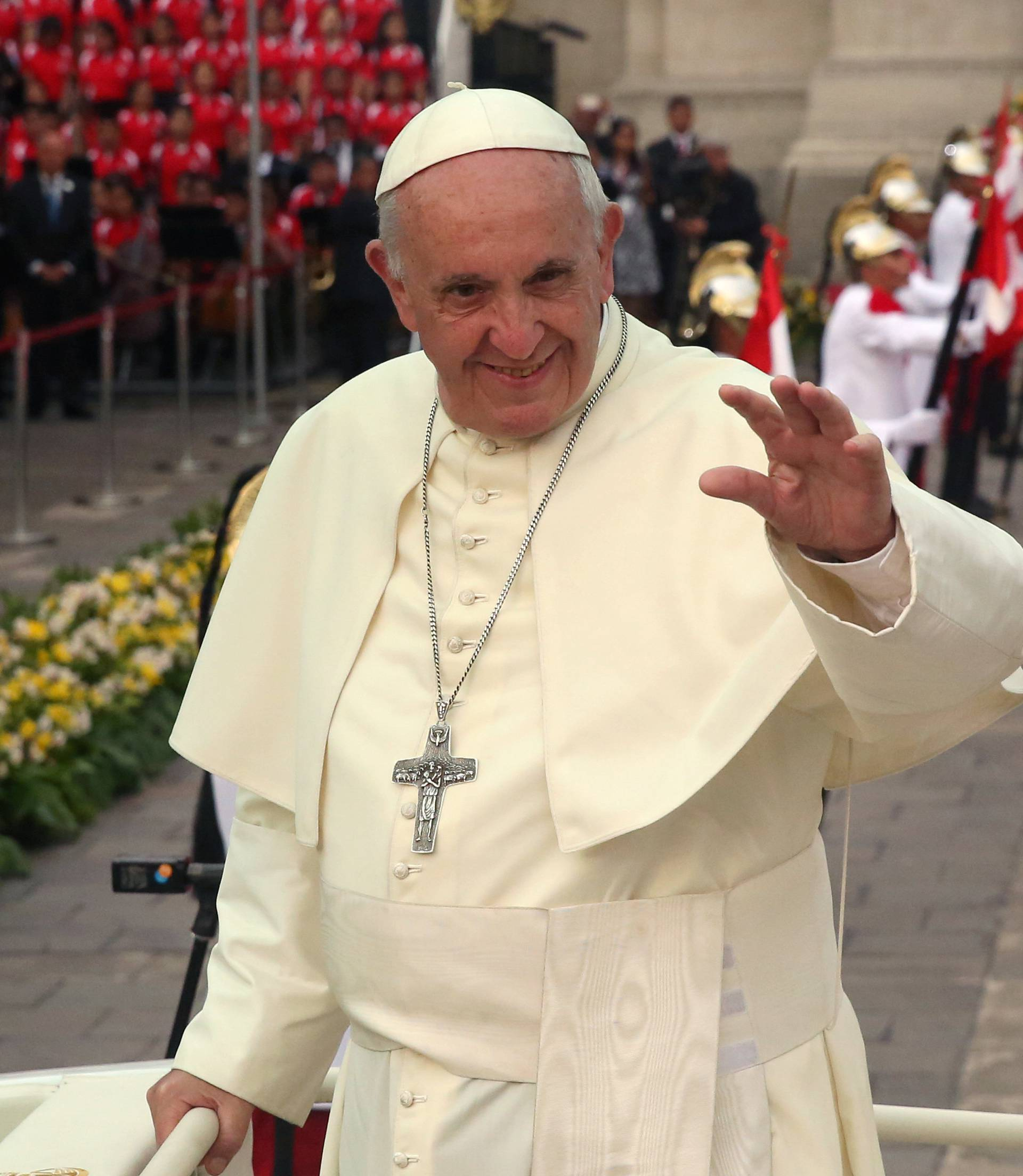Pope Francis waves as he leaves the presidential palace in Lima