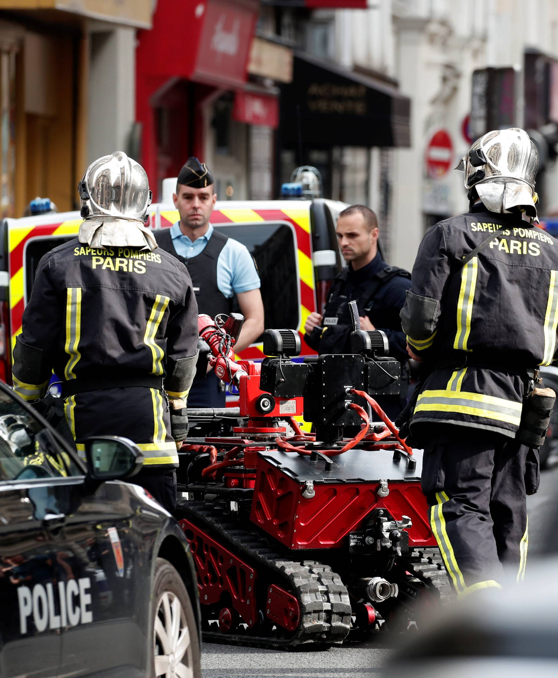 French police and special police forces (BRI) and firemen secure the street as a man has taken people hostage at a business in Paris