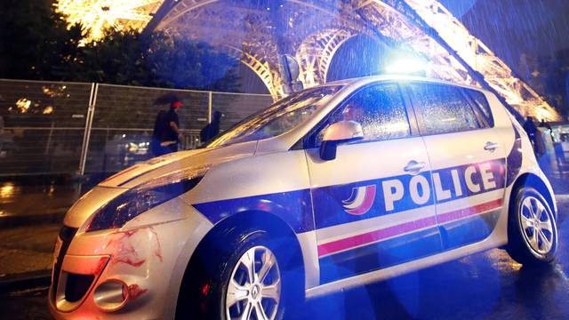 A police car is seen parked in front of the Eiffel Tower in Paris