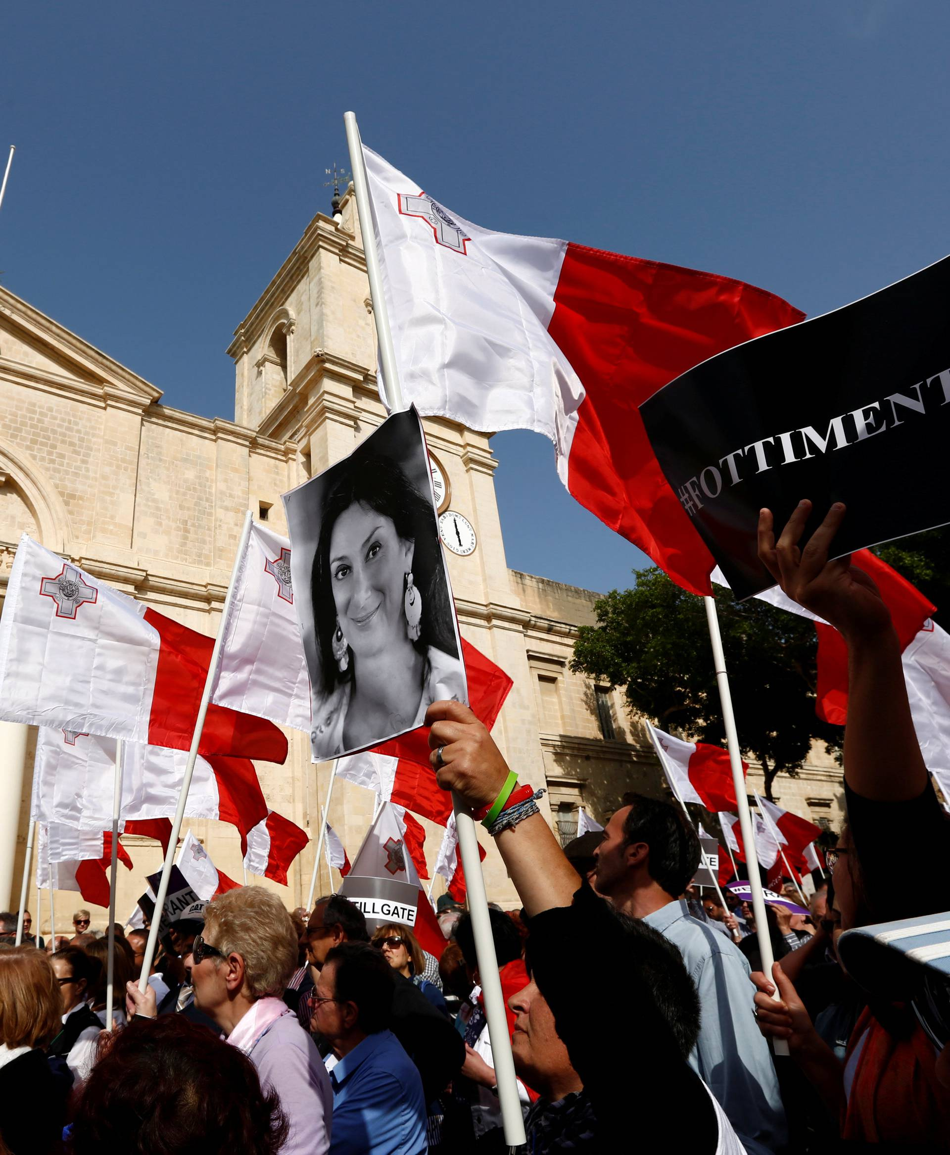 A demonstrator carries a photo of assassinated anti-corruption journalist Daphne Caruana Galizia during a protest against government corruption in light of the revelations in the Daphne Project, in Valletta