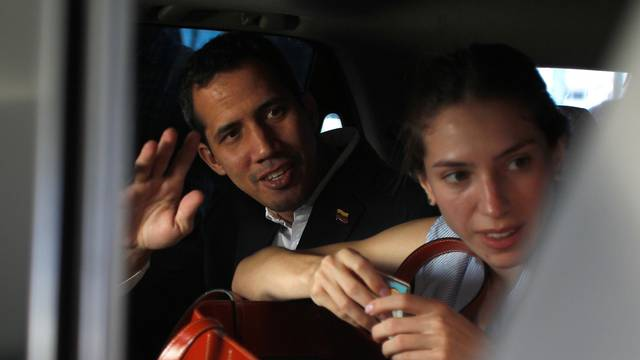 Venezuelan opposition leader Juan Guaido, who many nations have recognized as the country's rightful interim ruler, waves next to his wife Fabiana Rosales while leaving a hotel in Salinas