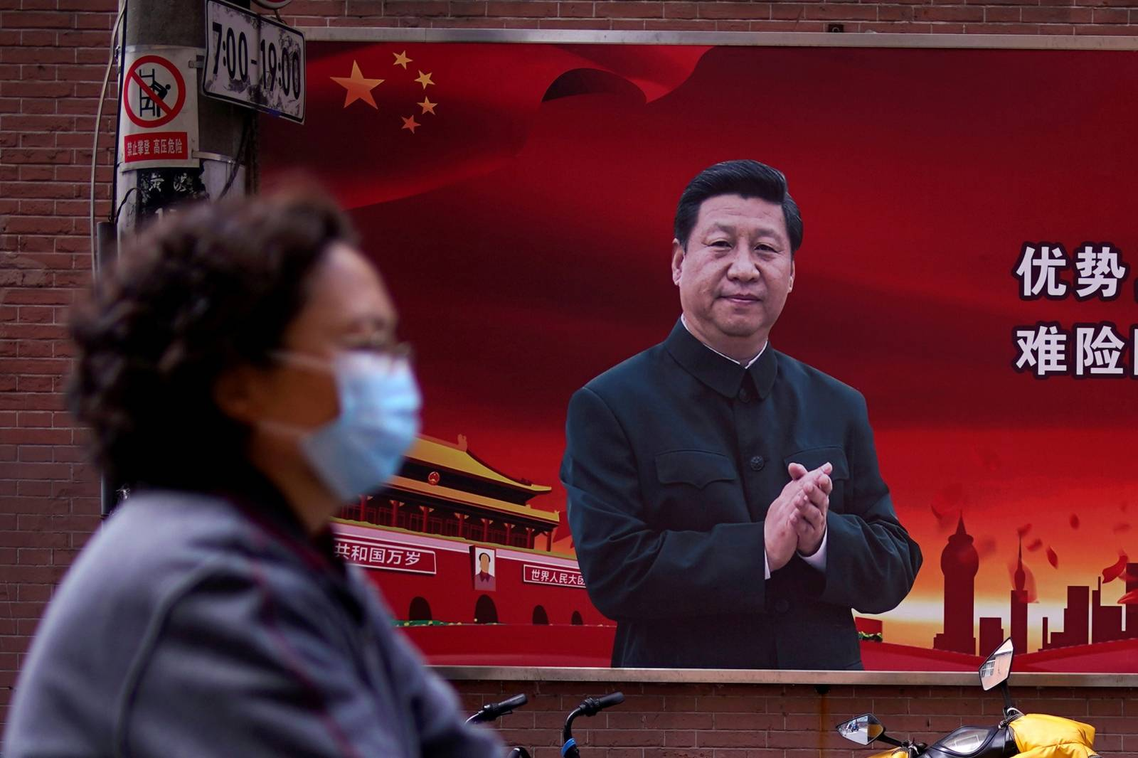 FILE PHOTO: Woman wearing a protective mask is seen past a portrait of Chinese President Xi on a street as the country is hit by an outbreak of the coronavirus, in Shanghai
