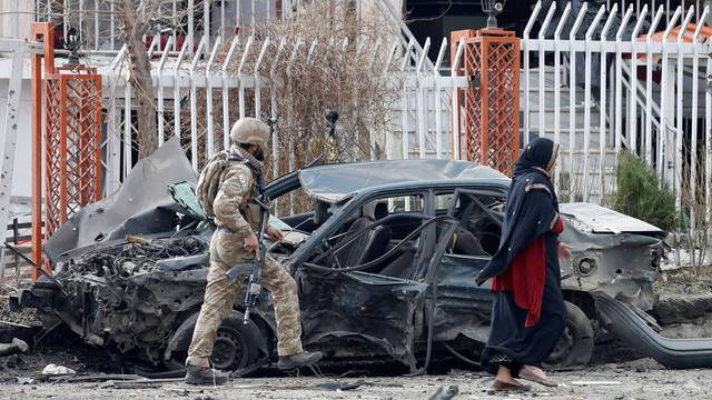 A member of Afghan security forces inspects a damaged vehicle at the site of a blast in Kabul