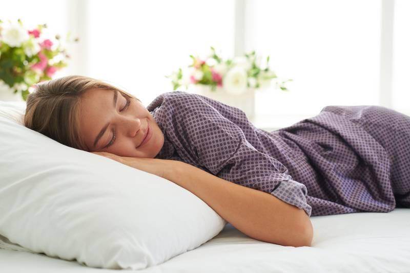 Close-up of beautiful woman in satin pajamas sleeping peacefully