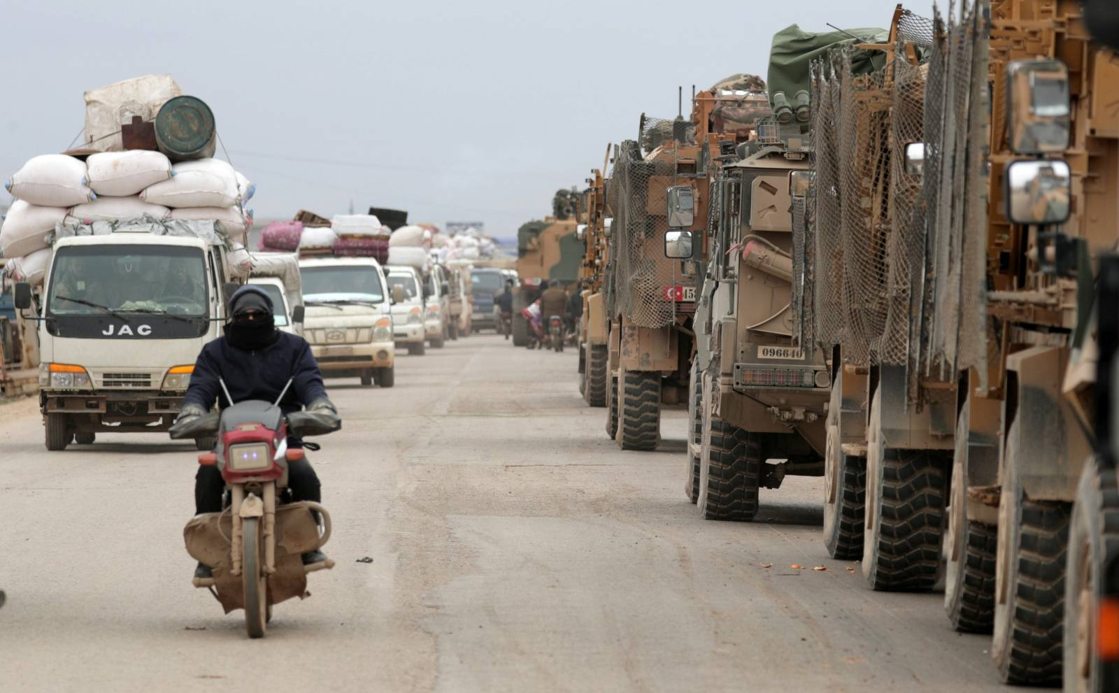 A man rides on a motorbike past Turkish military vehicles in Hazano near Idlib