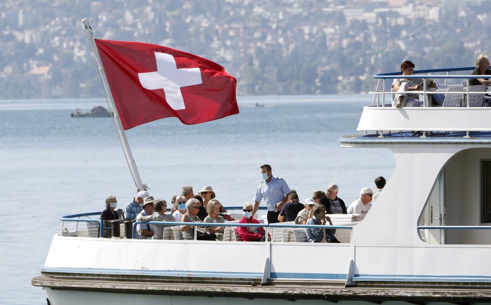 Switzerland's national flag flies above passengers as tourist vessel Limmat sails on Lake Zurich in Zurich