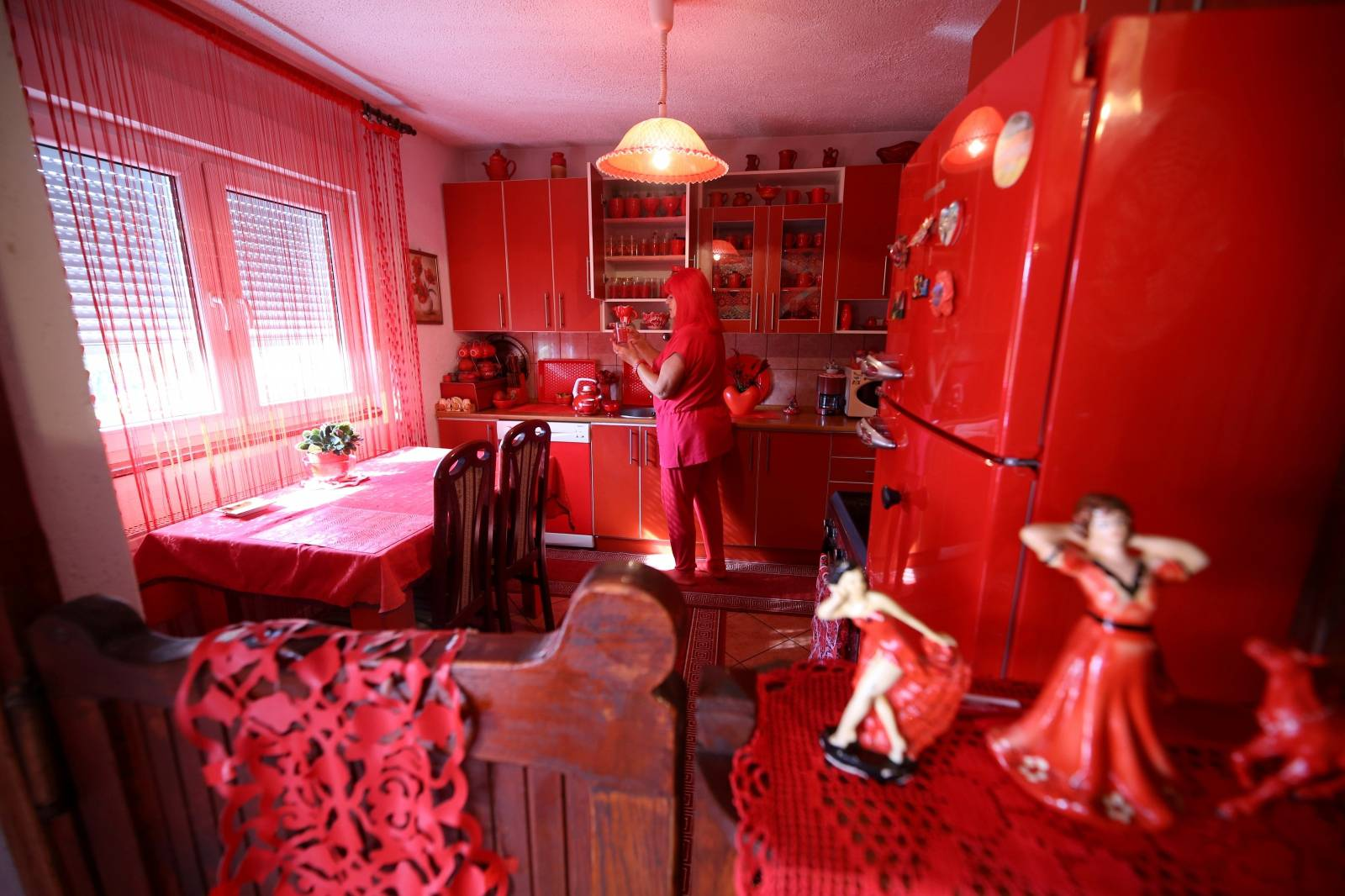 Zorica Rebernik, obsessed with the red color, stands in the kitchen inside her house in the village of Breze near Tuzla
