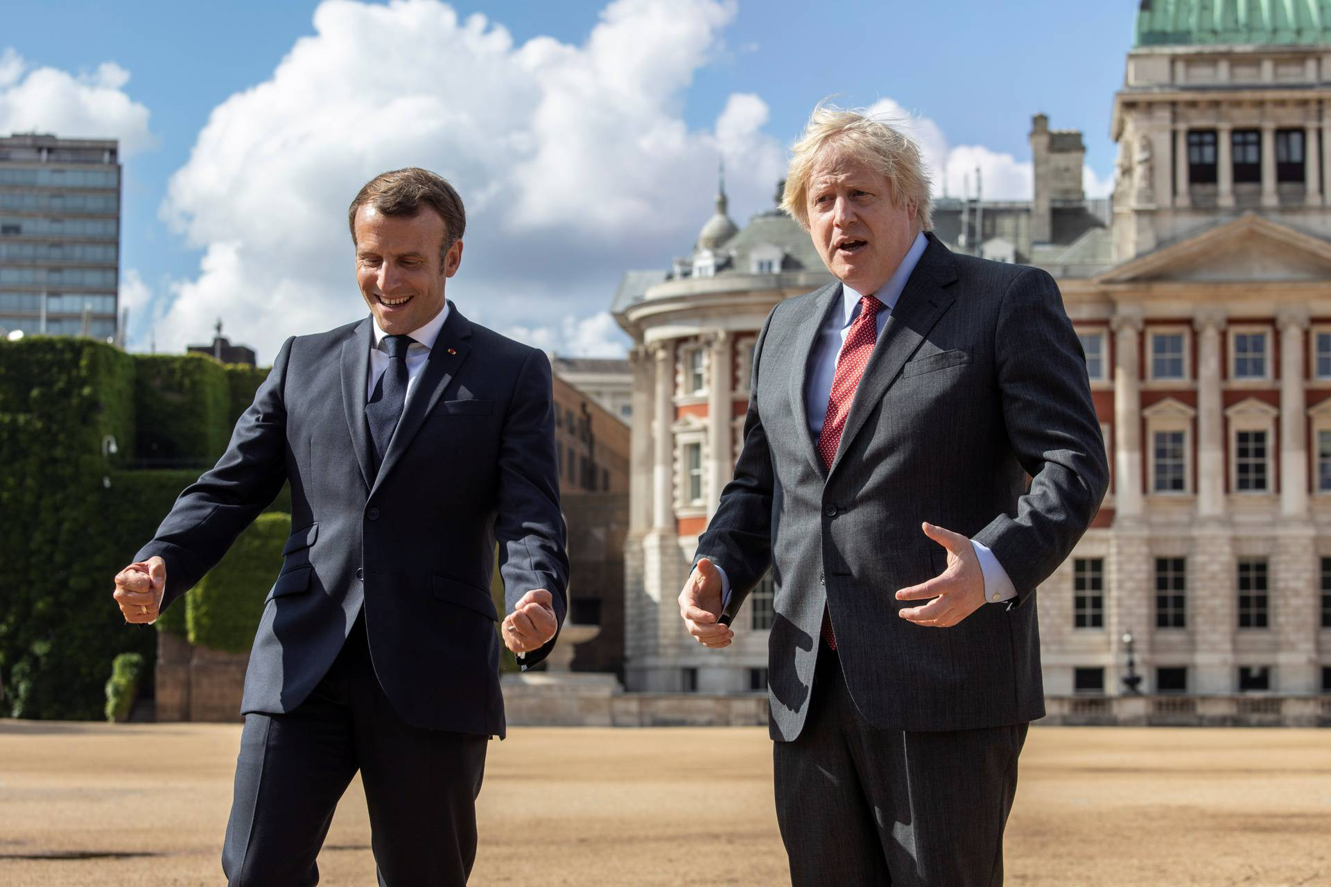 British Prime Minister Boris Johnson and French President Emmanuel Macron react after watching The Red Arrows and La Patrouille de France perform a flypast, at Horse Guards Parade in London