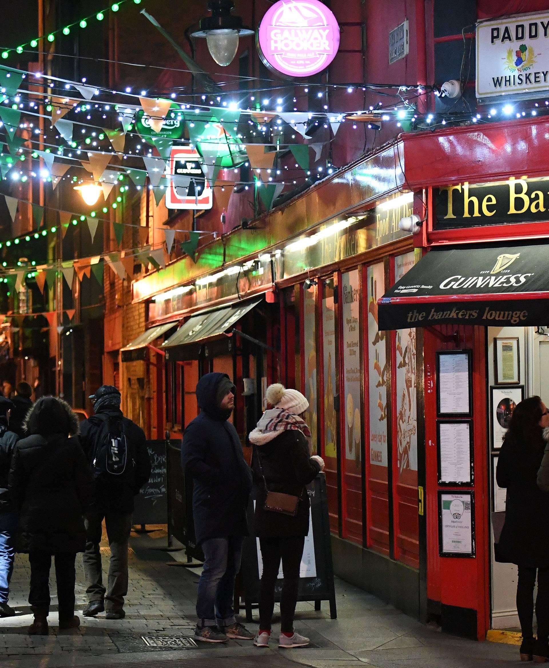 People walk under Christmas lights illuminating a street in Dublin