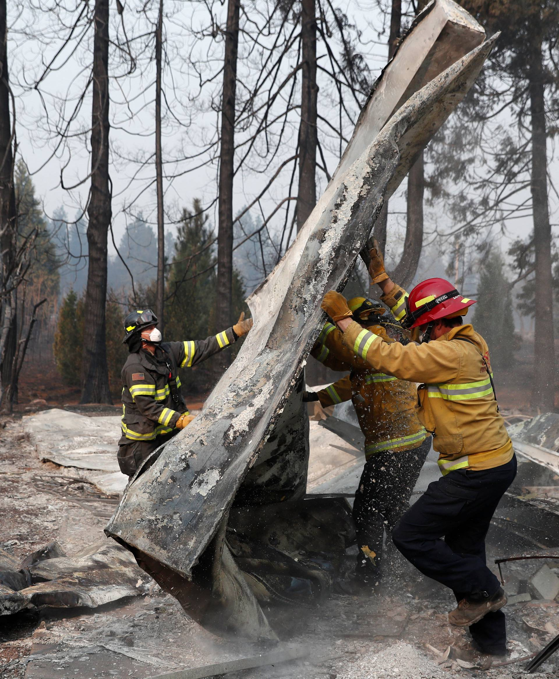 Firefighters move debris while recovering human remains from a trailer home destroyed by the Camp Fire in Paradise