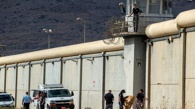 Israeli security personnel stand together outside the walls of Gilboa prison after six Palestinian militants broke out of it in north Israel