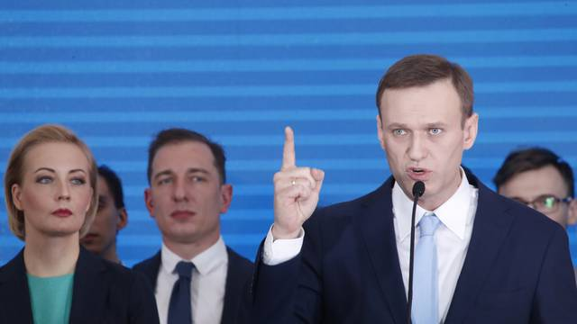 Russian opposition leader Alexei Navalny and his wife Yulia attend a meeting to uphold his bid for presidential candidate, in Moscow