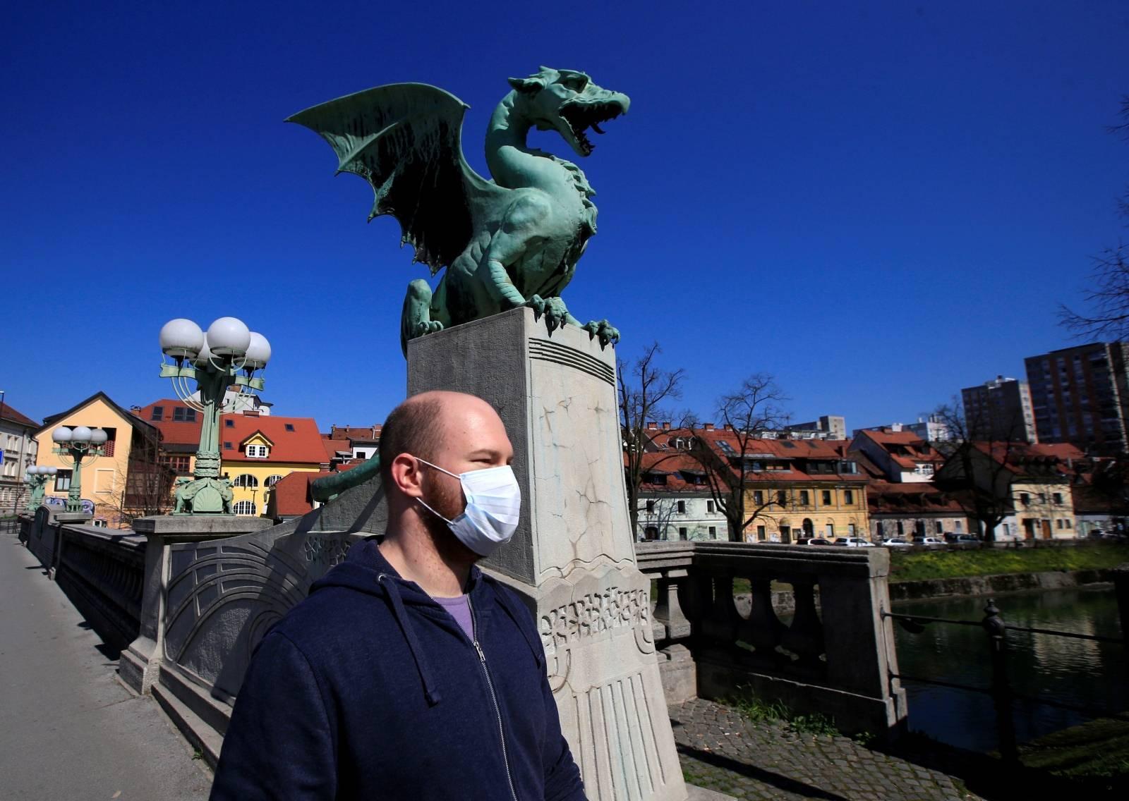 FILE PHOTO: A man with a face mask walks on the Dragon's bridge during coronavirus disease (COVID-19) fears, in Ljubljana