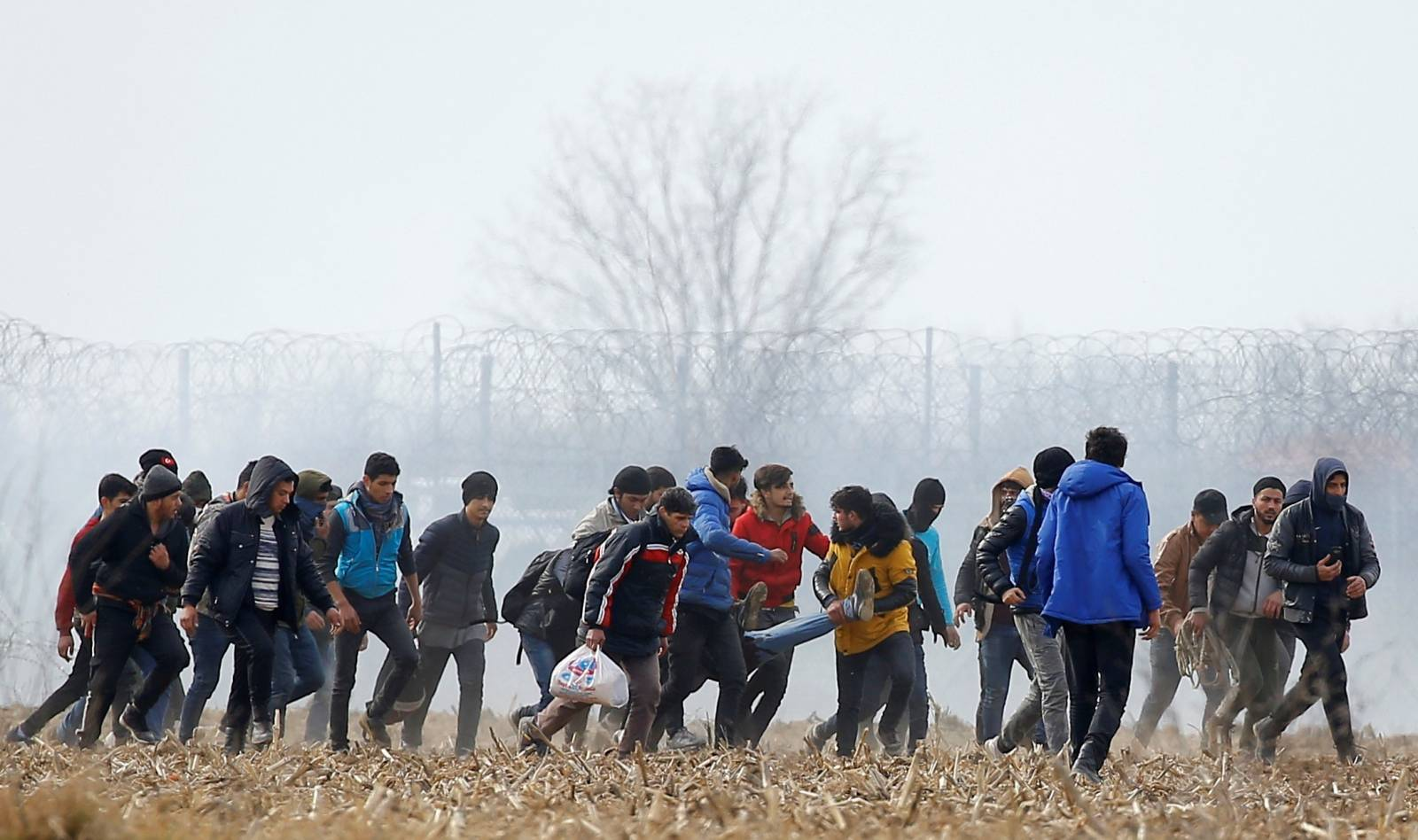Migrants carry an injured man near the Turkey's Pazarkule border crossing with Greece's Kastanies, near Edirne