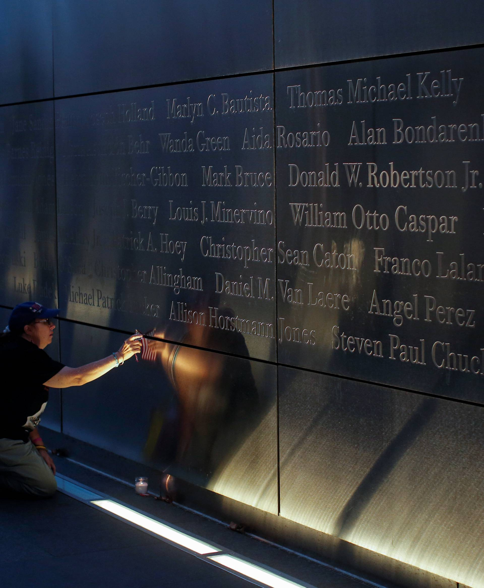 A mourner places a flag in the Empty Sky memorial on the morning of the 15th anniversary of the 9/11 attacks in New Jersey
