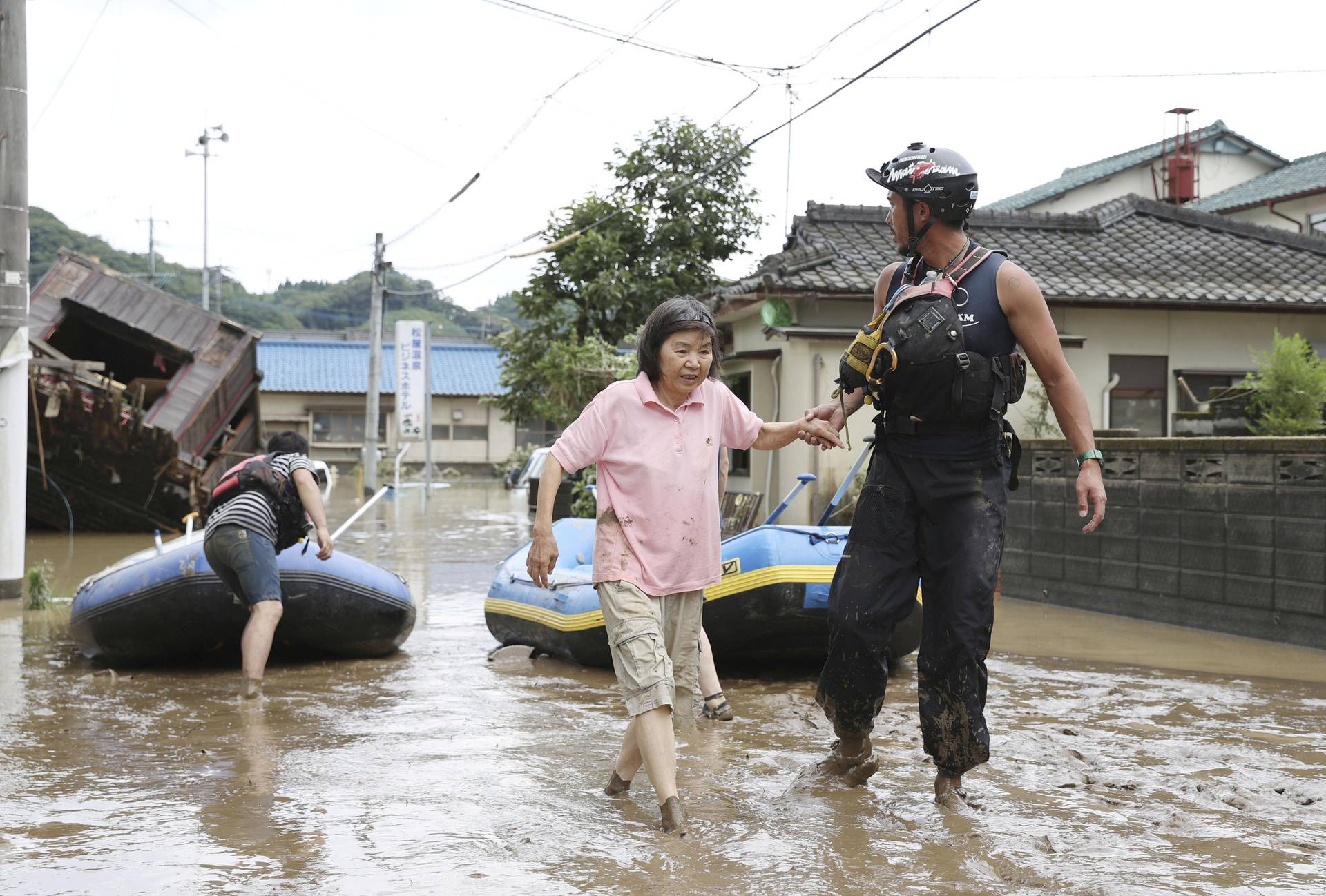 A rescue worker helps local residents at a flooded area caused by a heavy rain along Kuma River in Hitoyoshi, Japan