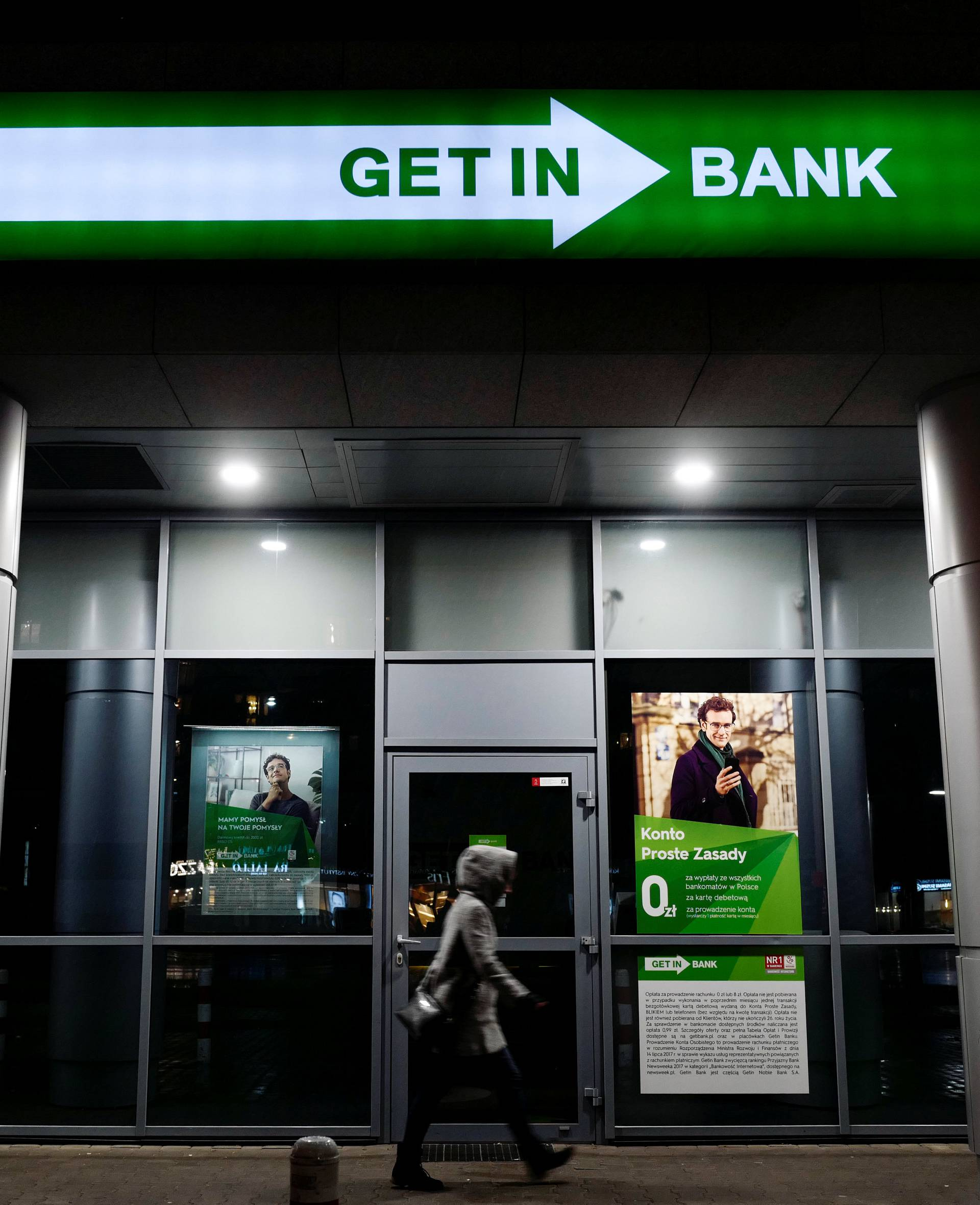 A woman passes Getin Noble Bank branch in Warsaw