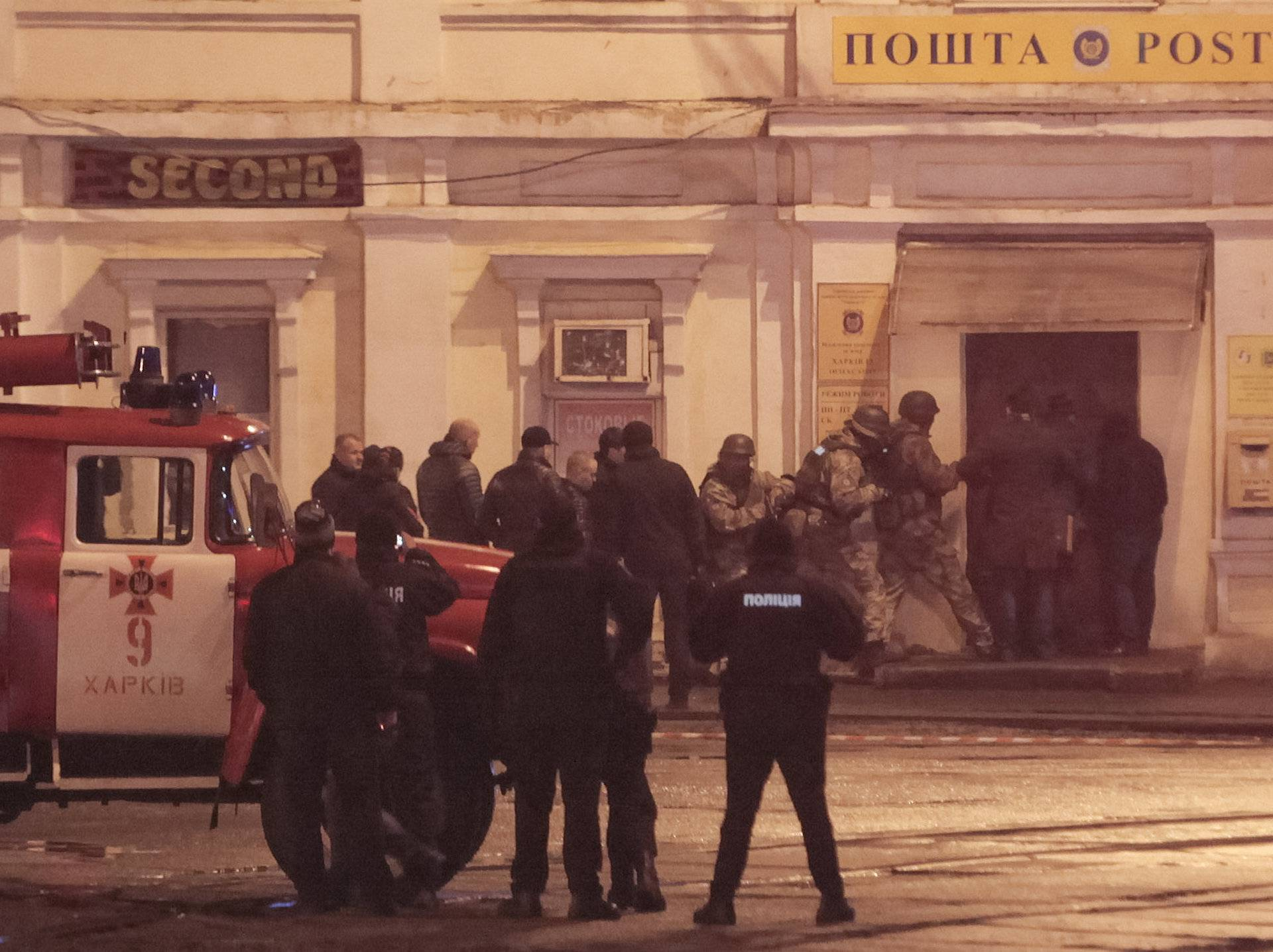 Members of a police special operations unit gather outside a post office, where a man took people hostage, in Kharkiv