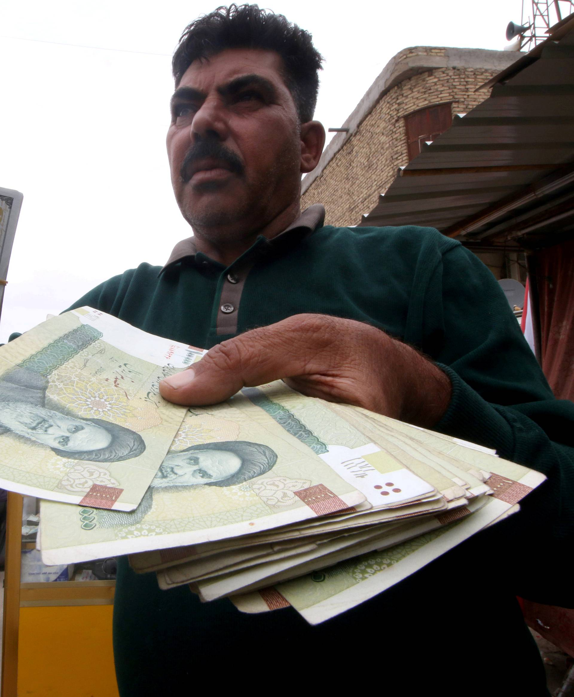 FILE PHOTO: A man holds Iranian rials at a currency exchange shop, before the start of the U.S. sanctions on Tehran, in Basra